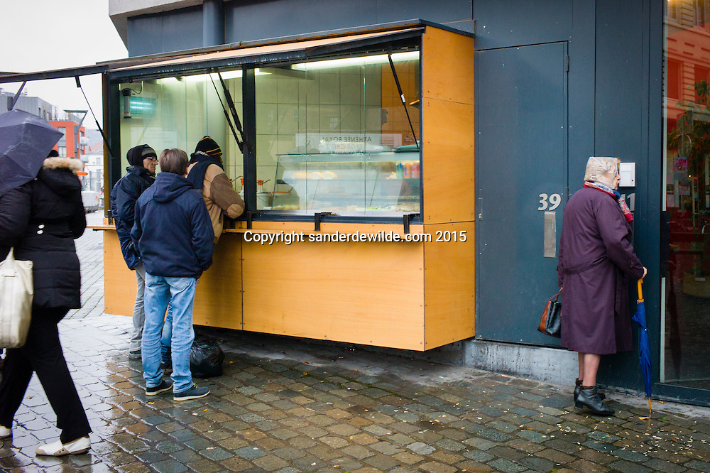 Belgium, Brussels, Sint Jans Molenbeek. 11 December 2015.  Molenbeek, the community of Brussels where terrorists of the Paris attacks lived. A typical fritkot (selling French fries and other snacks built in a wall, where an older woman tries entering a building and a moslima with umbrella passes by. (Sander de Wilde for National Post)(For story by Matthew Fischer, foreign correspondent)