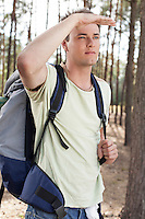 Young man with backpack shielding eyes in forest