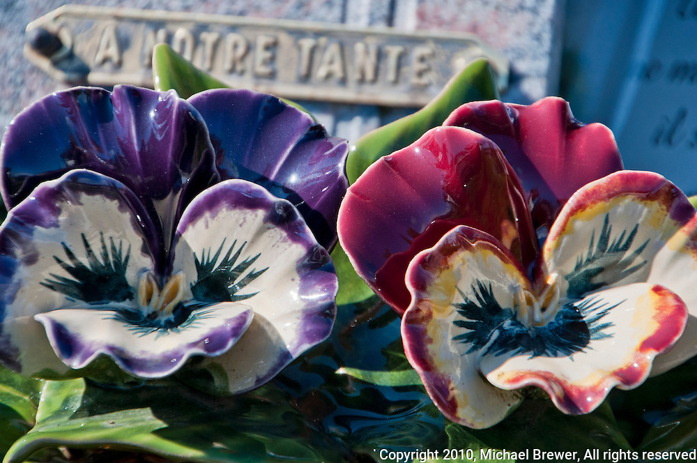 Close-up of pretty ceramic majolica pansies - A notre Tante - on a grave in Provence, France.