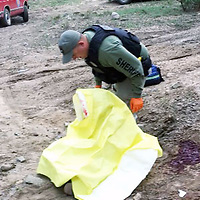 A Cibola County Sheriff's Department deputy assists one of the victims in a Saturday crime spree in Cibola County.