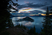 A hint of golden sunrise color shines through the dark storm clouds hovering over Wizard Island and Crater Lake in Crater Lake National Park, Oregon. Crater Lake, the deepest fresh water lake in North America, is located in a caldera at the top of what was once Mount Mazama. A massive eruption around 5,700 B.C. caused the mountain to collapse. While the Wizard Island cone is long dormant, there is some hydrothermal activity at the bottom of Crater Lake, suggesting the mountain is still active.