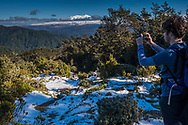 Matthew taking pics with his snow, probably doing  snapchat, distant view of Mt Ruapehu.