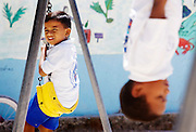 CAYE CAULKER, : March 16, 2006 -- CAYE CAULKER, BELIZE -- A schoolboy at Caye Caulker Catholic School lookes out from his perch on the swings before the afternoon session starts in  Caye Caulker, a small island off Belize March 16....Steve McKinley Photo.