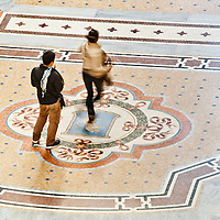 Elevated view of Galleria Vittorio Emanuele II in Milan on May 2, 2012. Pictured here is the very famous bull mosaic on the gallery pavement and the auspicious ritual of placing the heel on the bull's testicles and spinning. The picture, taken from a hardly accessible balcony, offers a unique view of the gallery from above