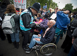© London News Pictures. 20/10/2012. London, UK. A policeman talks to a demonstrator while a group of demonstrators in wheelchairs block Park Lane in London during a mass rally organised by the TUC (Trades Union Congress) on October 20, 2012 to protest against the government's austerity policies and call for an alternative economic strategy. The march is followed by a rally in Hyde Park in which Labour Party Leader Ed Miliband will speak. Photo credit : Ben Cawthra /LNP