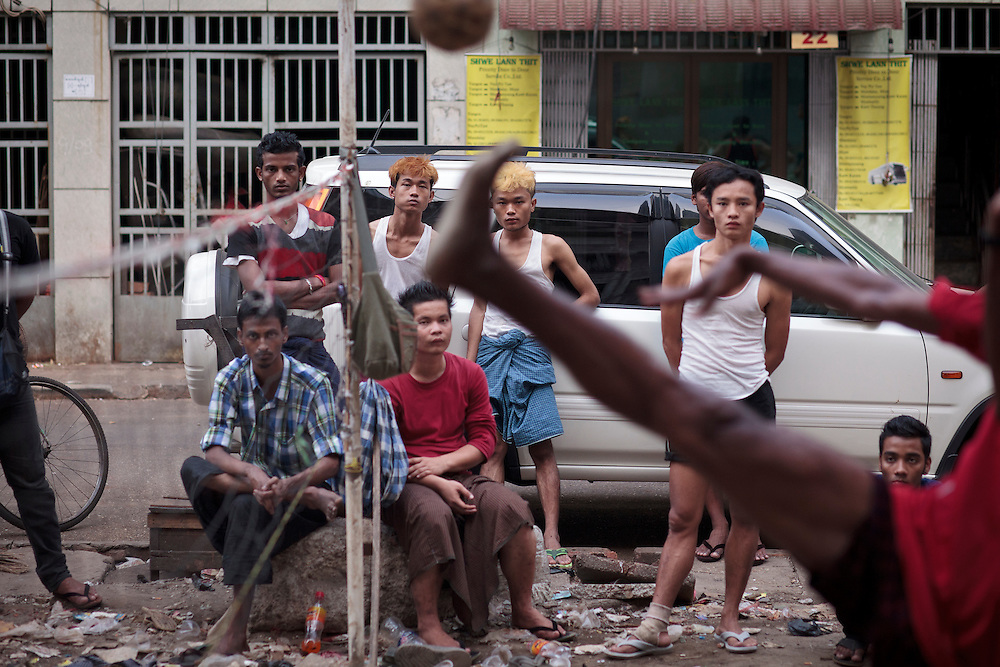 Burmese men play chinlone (national sport) on a laneway in Yangon, Yangon division, Myanmar.