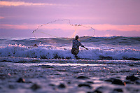 Young man fishing with a throw net at sunset along the coast of Michoacan, Mexico.<br />