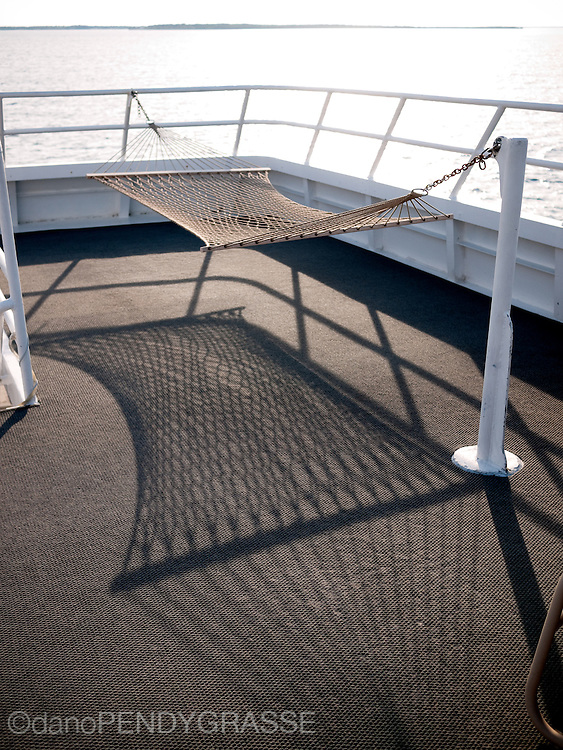 An empty hammock on the top deck of a liveaboard dive boat in Belize.