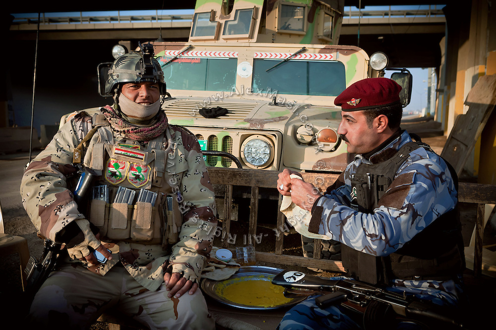 An Iraqi soldier (left) and a member of the Iraqi Police (right) are sitting next to a Humvee vehicle, guarding the main checkpoint to the city of Fallujah, Iraq, on Highway N.10. (Baghdad-Fallujah-Ramadi)