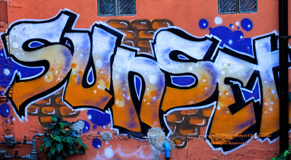 """A wall down a dark back alley is adorned with the bright orange and blue graffiti with the word """"Sunset"""", Chiang Mai Thailand."""