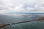 Nederland, Zeeland, Oosterschelde, 22-05-2011; Oosterscheldekering, stormvloedkering tussen Schouwen en Noord-Beveland.  Sluitgat Schaar, met de voormalige werkhavens bij werkeiland Neeltje Jans. Links van de kering de Oosterschelde, onder in beeld de Noordzee. Walcheren aan de verre horizon..Storm surge barrier in Oosterschelde (East Scheldt), between Islands of Schouwen-Duiveland and Noord-Beveland. North Sea on the right side of the barrier (below). Under normal circumstances the barrier is open to allow for the tide to enter and exit. In case of high tides in combination with storm, the slides are closed..luchtfoto (toeslag); aerial photo (additional fee required);.foto Siebe Swart / photo Siebe Swart