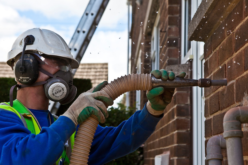 Cavity wall insulation is being installed in a home in Kirklees, UK. Holes are drilled into the wall and foam pumped in.