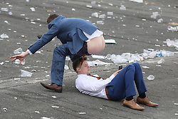 © Licensed to London News Pictures. 08/04/2016. Liverpool, UK. A racegoer bares all in the face of another at the end of Ladies Day at the Grand National 2016 at Aintree Racecourse near Liverpool. The race, which was first run in 1839, is the most valuable jump race in Europe. Photo credit : LNP