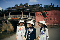 Three tourists walk around the Old Town of Hoi An, Vietnam wearing traditional dresses.