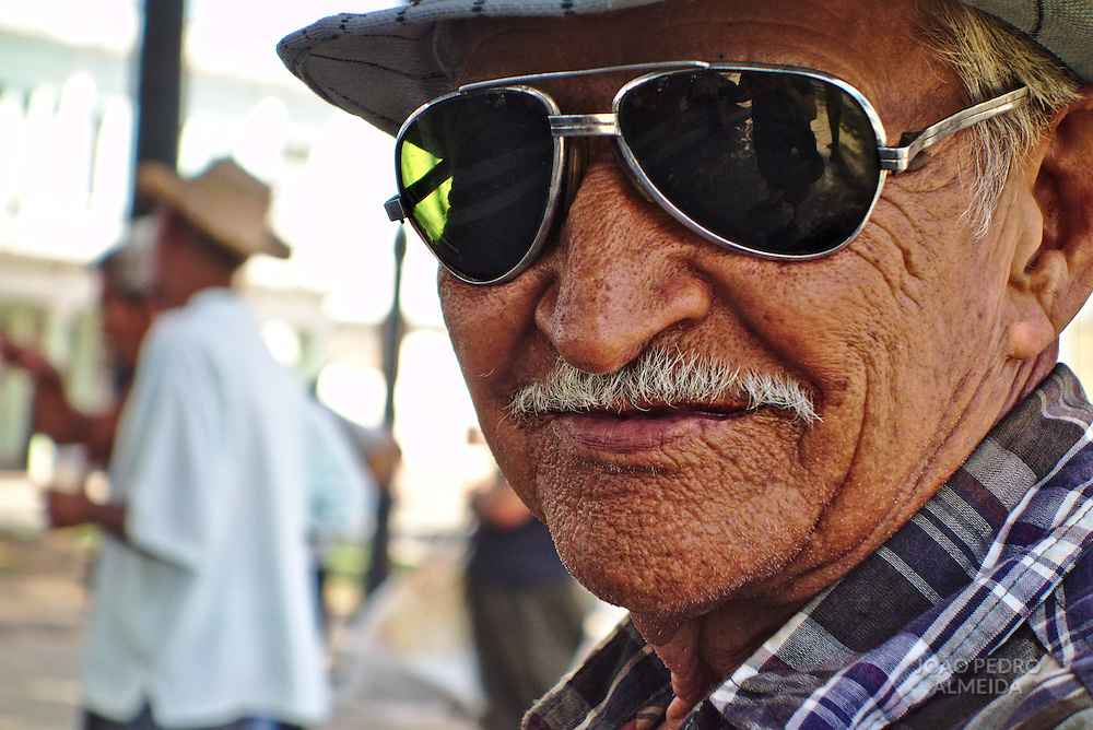 A stylish elderly man waiting for a concert at a garden of Cienfuegos