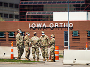 "26 APRIL 2020 - DES MOINES, IOWA: Soldiers with the Iowa Army National Guard wait for people to arrive at the COVID-19 drive through testing site in Des Moines. Iowa started mass testing Saturday, with a drive through testing site in a parking lot in downtown Des Moines. The testing this weekend is considered a ""soft opening"" for the program and tests were reserved for medical professionals and first responders. Despite numerous outbreaks in meat packing plants throughout Iowa, members of the public have not been able to get tested. On Saturday, 25 April, there were 5,092 confirmed cases of COVID-19 (Coronavirus / SARS-CoV-2) in Iowa (an increase of 647 since Friday, April 24) and 112 deaths in Iowa caused by COVID-19.          PHOTO BY JACK KURTZ"
