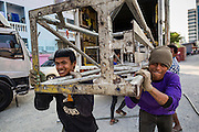 19 JANUARY 2014 - BANGKOK, THAILAND:  Members of the crew unload stage rigging from a truck before a mor lam show in Khlong Tan Market in Bangkok. Mor Lam is a traditional Lao form of song in Laos and Isan (northeast Thailand). It is sometimes compared to American country music, song usually revolve around unrequited love, mor lam and the complexities of rural life. Mor Lam shows are an important part of festivals and fairs in rural Thailand. Mor lam has become very popular in Isan migrant communities in Bangkok. Once performed by bands and singers, live performances are now spectacles, involving several singers, a dance troupe and comedians. The dancers (or hang khreuang) in particular often wear fancy costumes, and singers go through several costume changes in the course of a performance. Prathom Bunteung Silp is one of the best known Mor Lam troupes in Thailand with more than 250 performers and a total crew of almost 300 people. The troupe has been performing for more 55 years. It forms every August and performs through June then breaks for the rainy season.              PHOTO BY JACK KURTZ