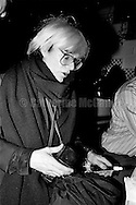 December 31, 1986:  Andy Warhol gets ready to blow a noise maker and celebrate his last New Year's Eve with a dinner at Cafe Roma restaurant in New York City, New York.  Warhol died less than two months later on February 22, 1987..