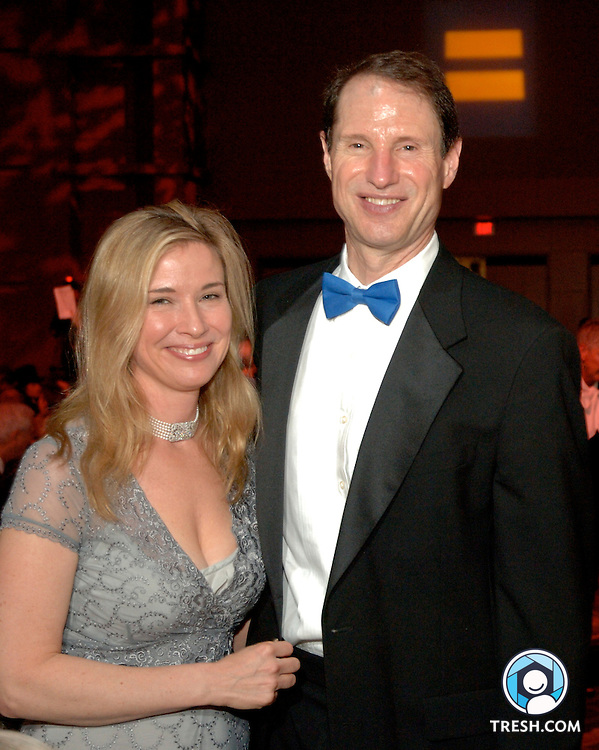 U.S. Senator Ron Wyden of Oregon and his wife Nancy at the Tenth Annual HRC National Dinner. The HRC logo is illuminated in background.