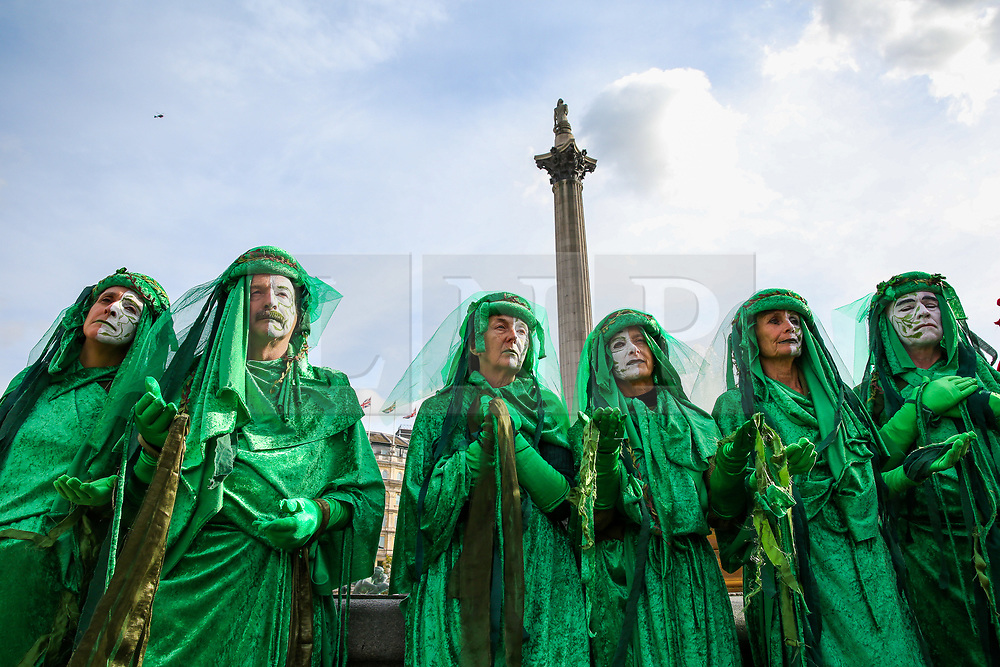 © Licensed to London News Pictures. 09/10/2019. London, UK. The Red Brigade of The Invisible Circus dressed in green with white makeup protest under Nelson's Column on day three of the two weeks protest in Westminster. The activists are calling for the government to act on climate change. Photo credit: Dinendra Haria/LNP