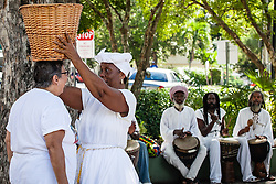 "Mary Ann Christopher ""Queen Coziah"", places the coal basket on the head of Justine A. Mis to demonstrate it's weight.  7th Annual Dollar Fo' Dollar Culture & History Tour & MIni Coaling Exhibit.  A remebrance of the 1892 Coal Workers Strike on St. Thomas ""livicated"" to Ras Jahstarr Koniyah.  Held annually in September, the tour celebrates the successful protest of 19th centry coal laborers in the streets of downtown Charlotte Amalie for better pay.  Mary Ann Christopher plays the role of Queen Coziah who led the successful revolt.  © Aisha-Zakiya Boyd"