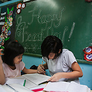 An older girl helps a younger one doing her home work. It is Monday morning but due to heavy rains school has been cancelled. Laura Vicuña Foundation, Inc. provides a safe haven, a secure home for girls where they live together with sisters from the Don Bosco order. They get the love and care they never have received and counselling when needed from qualified psychotherapists. .The Laura Vicuña Centre in Cubao houses 30 street girls who may be orphaned, neglected, abandoned, battered, morally endangered and sexually abused.The girls are aged between 6 and 16 and all of them go to school in the local municipality.Laura Vicuña is a non-profit charity working in Manila and in Bacolod in the state Negros Occidental in the Philippines.