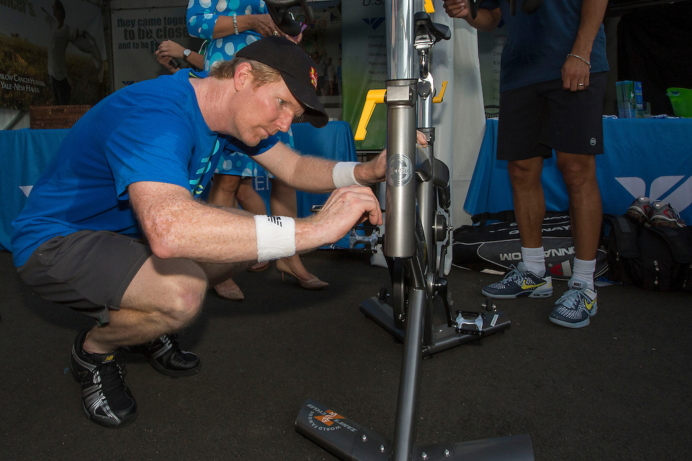 August 20, 2014, New Haven, CT:<br /> Jim Courier autographs a spin bikes at the Yale New Haven Health booth during the Men's Legends Event on day six of the 2014 Connecticut Open at the Yale University Tennis Center in New Haven, Connecticut Wednesday, August 20, 2014.<br /> (Photo by Billie Weiss/Connecticut Open)
