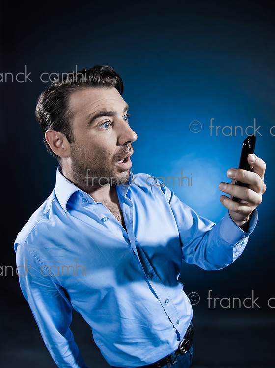 caucasian man looking at phone stun unshaven portrait isolated studio on black background