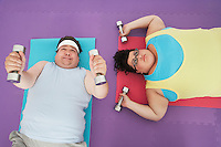 Overweight man and woman lying down lifting dumbbells overhead view
