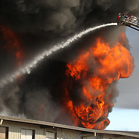 The lone ladder truck from Pontotoc struggles to conatin the fire at American Furniture on Friday in Ecru.