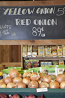 Yellow onions on display with blackboard in background