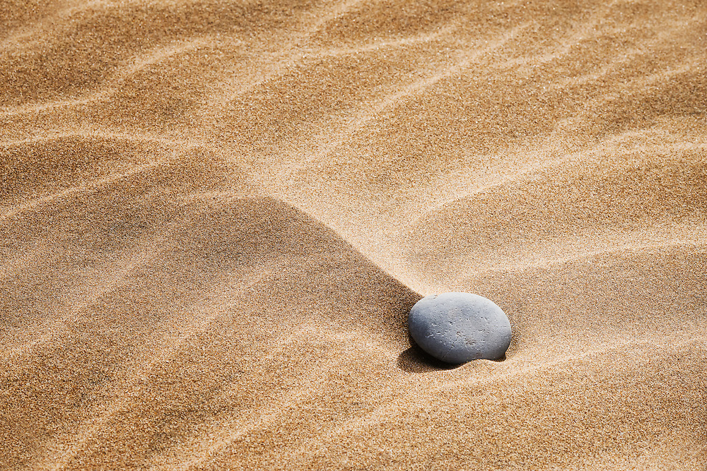 Stone in sand at the sand dunes of Lagoon Khenifiss (Lac Naila).