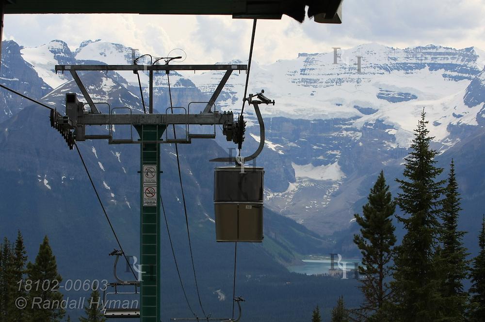 Ski resort gondolas give summer visitors a sightseeing ride above Lake Louise and surrounding mountains;  Banff National Park, Alberta, Canada.