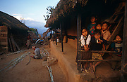 A group of young Nepali children stand on the terrace of a small hut where they live in the village of Rip in the Gorkha district of central Nepal, one of the 75 districts of modern Nepal. The kids gaze into many directions while two village elders attend to domestic chores in the dirt. Beyond them, we see snow capped peaks of Himalayan mountains. Gorkha has lent its name to the Gurkha soldier, from where young teenage boys are typically recruited for service into the British army, a tradition that goes back to the Indian Mutiny of 1857