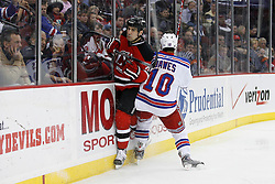 Feb 9, 2009; Newark, NJ, USA; New Jersey Devils defenseman Mike Mottau (27) gets hit by New York Rangers left wing Nigel Dawes (10) during the third period at the Prudential Center. The Devils defeated the Rangers 3-0.