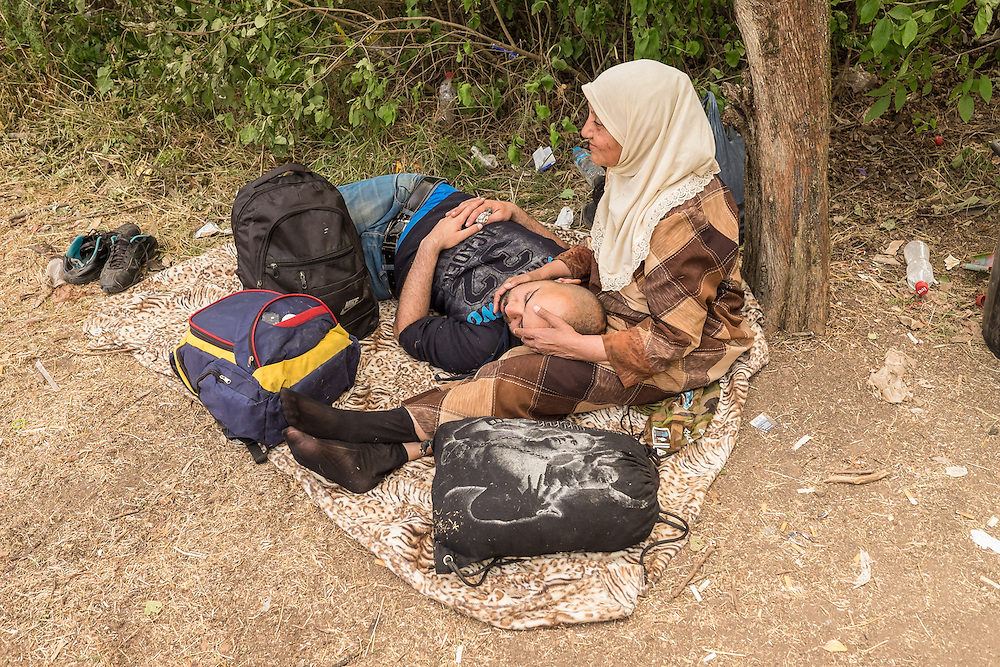 """Refugees from Syria rest at a """"one stop"""" camp set up by the Serbian Commissariat for Refugees and Migration in the town of Presevo, near the the country's border with Macedonia."""