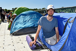 "© Licensed to London News Pictures. 30/06/2018. LONDON, UK.  Darius Platt-Vowles from Gloucestershire poses in his tent in Wimbledon Park.  He is the first in ""The Queue"" for premium tickets, having arrived on Thursday 28 June, four days before the Wimbledon tennis championships are to begin on 2 July.  He hopes to be able to obtain tickets to centre court to see his idol, Roger Federer.  Behind him are Monique Hefti from Massachusetts (number 2 position) and Stefan Moser from Salzburg (number 3 position). Photo credit: Stephen Chung/LNP"