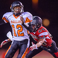 110113       Cable Hoover<br /> <br /> Gallup Bengal Cody Tabaha (12) looks for a receiver as Grants Pirate Jacob Willcox (24) closes in Friday at Grants High School.