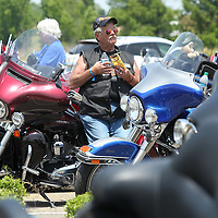 Adam Robison | BUY AT PHOTOS.DJOURNAL.COM<br /> Dane Van Pelt, of Albuquerque New Mexico, leans on his Harley as he takes a rest and has a snack and a bottle of water in the parking lot of the Tupelo Automiobile Museum Wednesday in Tupelo.