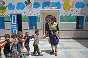 Tunisian Jewish school teacher Nrguila Achouche, ,21,leads her class of 3 and 4 year-old children in the courtyard of the Beit Rachel Kindergarten school located in the Hara Kebira  neighborhood on the Tunisian island of Djerba on May 25,2016.  Five years after Tunisia's revolution, and a year after three deadly ISIS attacks, the 1,100 Jews in this tiny island community of Djerba say they do not feel threatened living in Tunisia.(Photo by Heidi Levine).