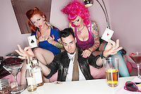 Man holding two playing cards with erotic females sitting besides him