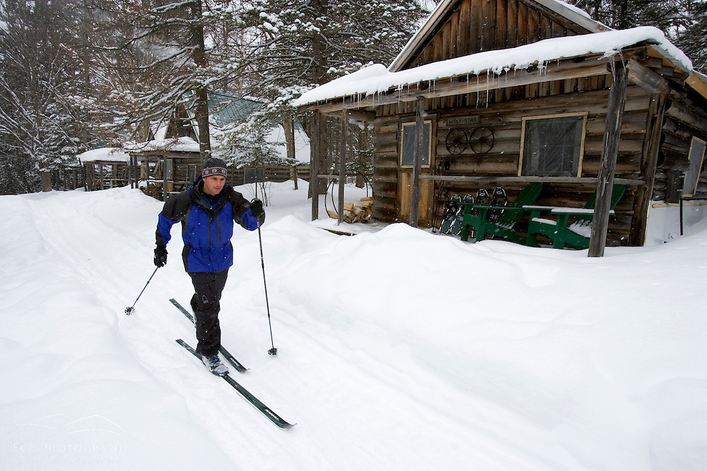 A skier makes his way past the visitor cabins at the AMC's Little Lyford Pond Camps in Maine's Northern Forest.