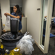 WASHINGTON, DC - DEC 11: Dinia Lovo Marquez, an 18-year-old senior at Bell Multicultural High School in Washington, DC, empties trash cans at the U.S. Department of Education, December 11, 2013, where she works as a janitor after school.  An immigrant from El Salvador, she one of 7 children being raised by her mother Maria, a cook at the Willard Hotel. Dinia wants to be the first in her family to attend college. (Photo by Evelyn Hockstein/For The Washington Post)