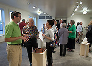 Ben Jensen (from left), executive director of The Ceramics Center talks with Lenonard Kallio and Carolyn Levine of Muscatine about a piece on artwork on display at the CSPS Hall Grand Re-opening in Cedar Rapids on Friday evening, August 26, 2011. About 190 people attended the event which featured a concert by Susan Werner.