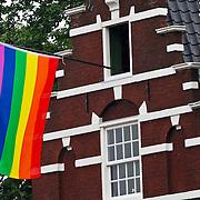 NLD/Amsterdam/20100807 - Boten tijdens de Canal Parade 2010 door de Amsterdamse grachten. De jaarlijkse boottocht sluit traditiegetrouw de Gay Pride af. Thema van de botenparade was dit jaar Celebrate, homovlag aan een Amsterdamse gevel