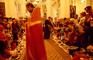 Parishoners bring cakes and decorated eggs to be blessed at Russian Orthodox Easter services.