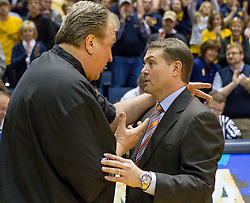 West Virginia Mountaineers head coach Bob Huggins and Oklahoma State Cowboys head coach Travis Ford talk after the game at the WVU Coliseum.