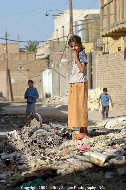 A young girl spies the photographer while she was playing with friends in a pile of garbage in the modernized center of the village Suq ash Shuyukh on the outskirts of Nasiriyah, Iraq, Sunday, August 3, 2003.  ..Since the 1991 uprising against Saddam Hussein in Shiite dominated Southern Iraq, people of this area have suffered greatly through his methods of disrupting daily life. For example, modernization came to a hault as money was diverted to Baath Party strongholds. Check points on on every other corner made it nearly impossible to go to work, the doctor, or visit family. Teachers made $5 U.S. per month and had to spend almost all of their salary for taxis in order to go to work...He tried to kill the people by cutting off the rivers that village survival depends on. Dams and canals dirverted the fresh water from flowing into the swamps by way of tributaries. In effect, without fresh water flowing in, the people started poisoning the water supply themselves by using it to wash and clean. Their primitive sewers still flow freely into the same waters that animals use and that feed their rice fields.