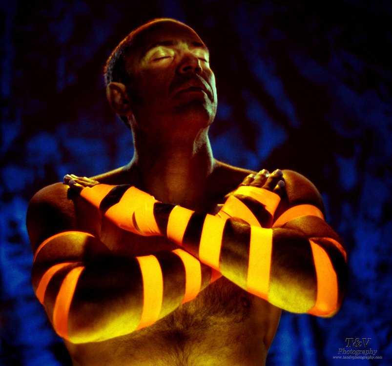 Man with glowing strips on arms and highlighted eyes.Black light