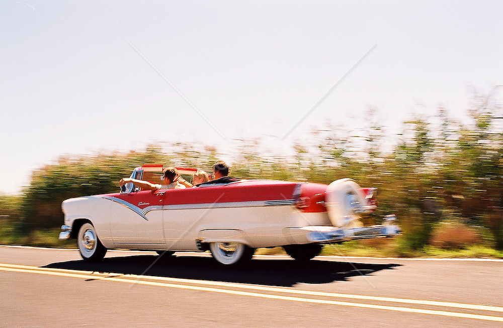 Friends riding in a classic convertible in East Hampton, NY
